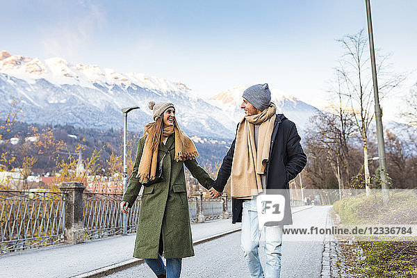 Austria  Innsbruck  happy young couple strolling together hand in hand at winter time