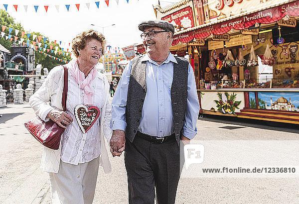 Happy senior couple walking hand in hand on fair