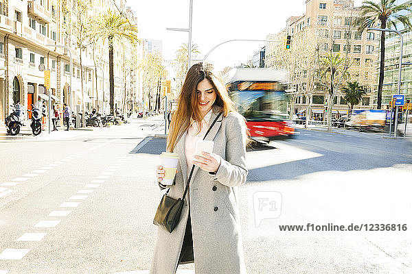 Spain  Barcelona  smiling young woman with coffee to go standing at roadside looking at cell phone