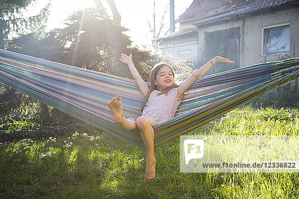Portrait of happy little girl sitting on hammock in the garden