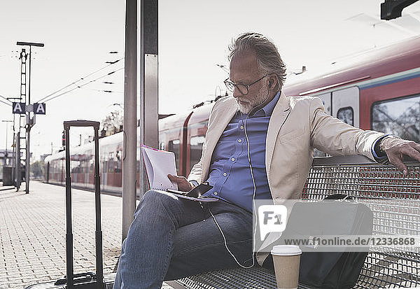 Mature businessman sitting at train station with cell phone  earbuds and notebook