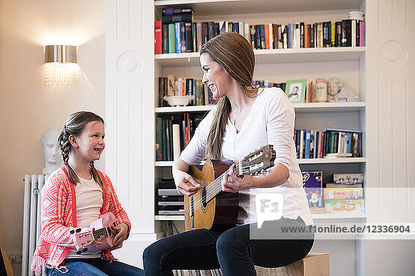 Mother and daughter playing guitar together at home