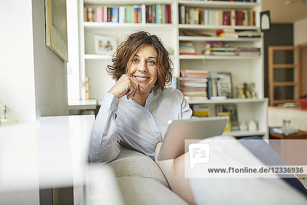 Portrait of smiling mature woman with tablet sitting on couch at home