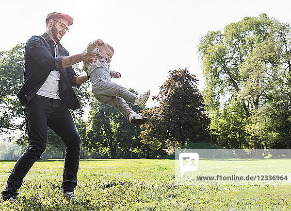 Happy father lifting up son in a park