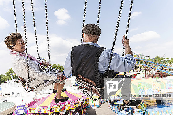 Senior couple hand in hand on chairoplane at funfair