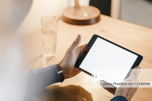 Close-up of man in a cafe holding tablet