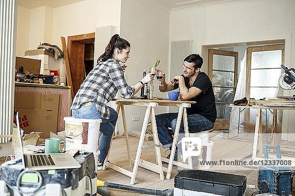 Happy couple renovating flat  taking a break  drinking read wine