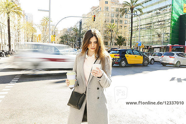 Spain  Barcelona  young woman with coffee to go standing at roadside looking at cell phone
