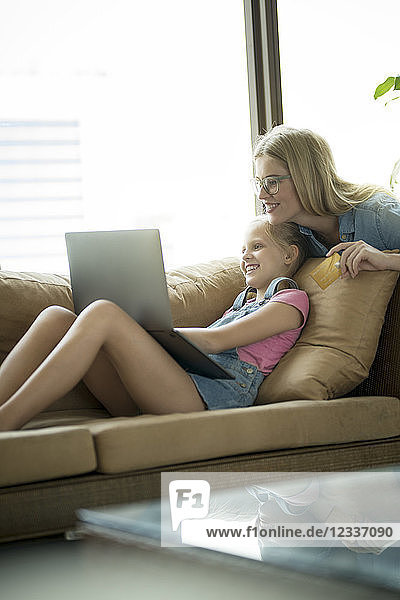 Mother and daughter in modern living room on a couch with laptop and credit card