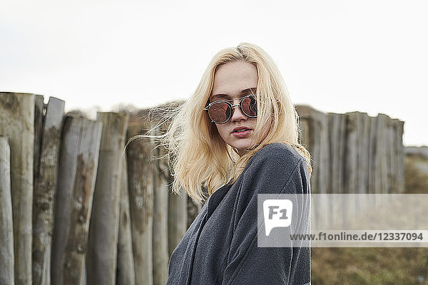 Portrait of blond young woman wearing mirrored sunglasses on the beach
