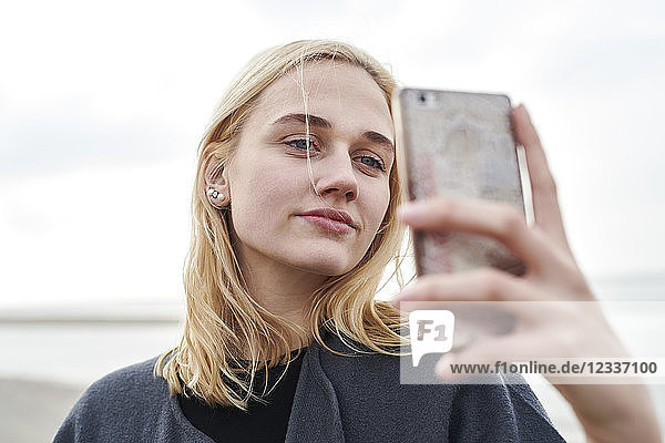 Portrait of blond young woman taking selfie with smartphone on the beach