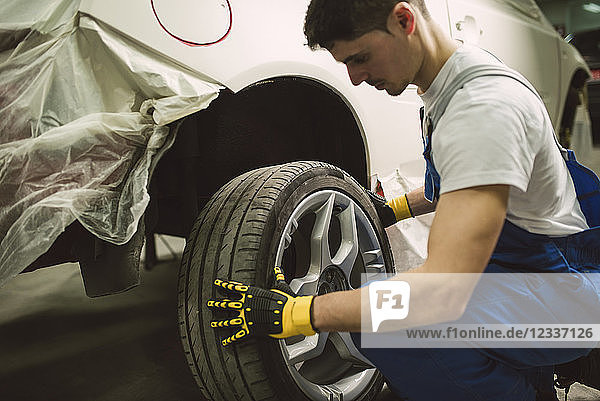 Mechanic changing car tyre in his workshop