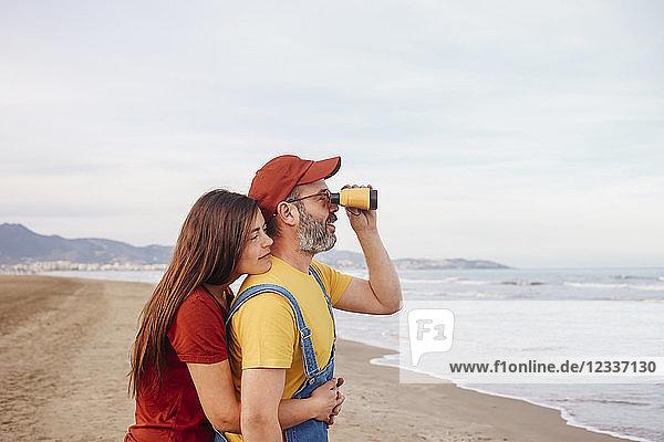 Couple with binoculars on the beach