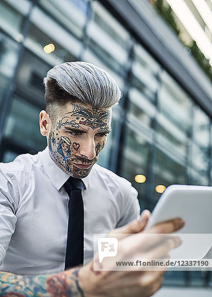 Young businessman with tattooed face  using digital tablet