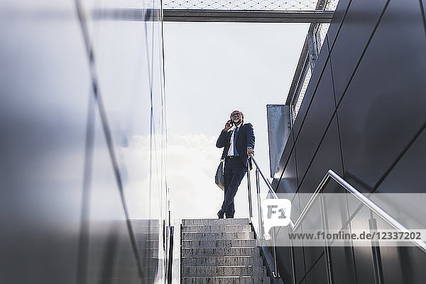 Smiling mature businessman at staircase in the city on cell phone