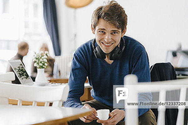 Portrait of smiling man in a cafe wearing headphones