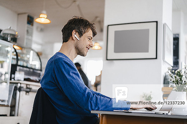 Smiling man in a cafe with earphone using laptop