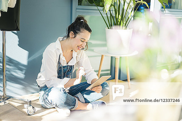 Smiling young freelancer sitting on the floor in her studio using tablet