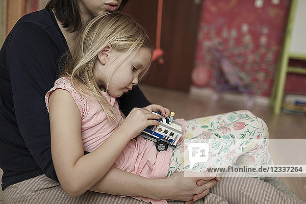 Mother and daughter  playing with toy car