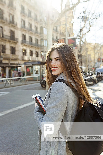Spain  Barcelona  portrait of smiling young woman with backpack standing at street