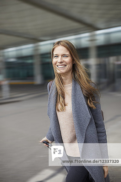 Portrait of confident businesswoman pulling suitcase at airport
