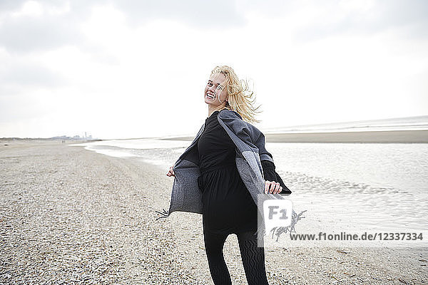 Netherlands  portrait of blond young woman running on the beach