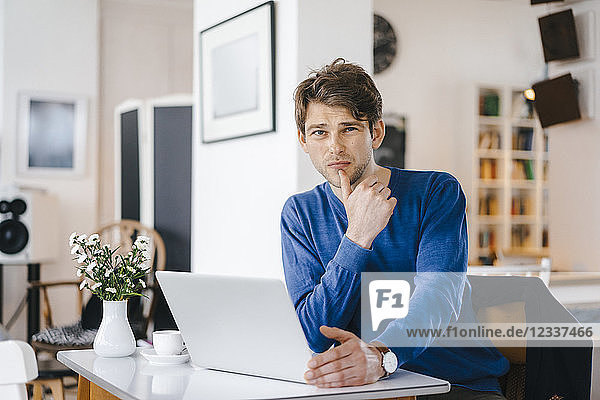 Portrait of man in a cafe sitting at table with laptop
