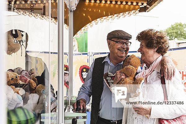 Happy senior couple with prize on fair