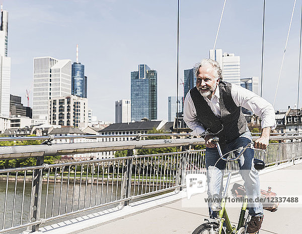 Happy mature man on bicycle crossing bridge in the city