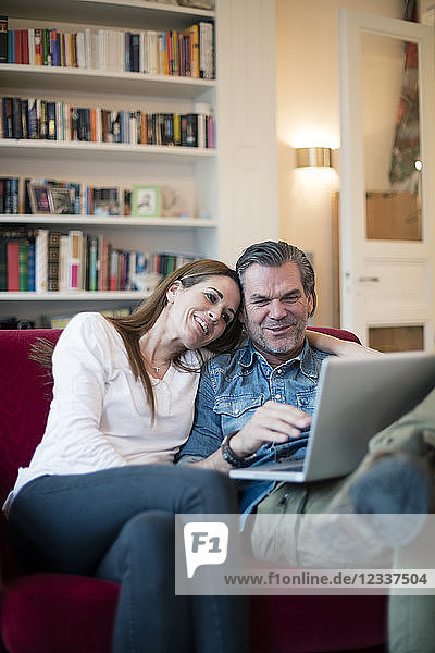 Happy couple sitting on couch using laptop