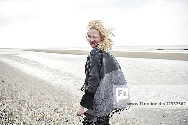 Netherlands  portrait of laughing blond young woman on the beach