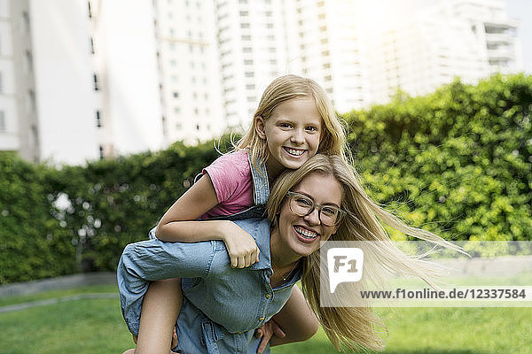 Portrait of happy mother and daughter in urban city garden