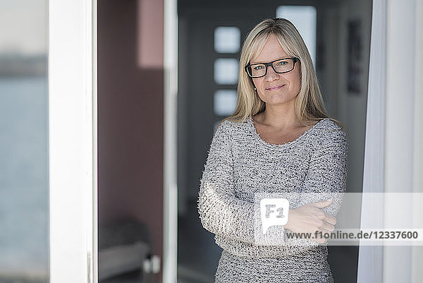 Woman with glasses staning in door with arms crossed