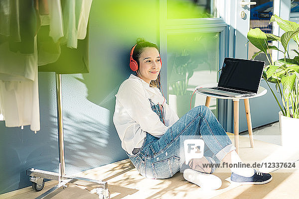 Smiling young freelancer sitting on the floor in her studio listening music with headphones and laptop