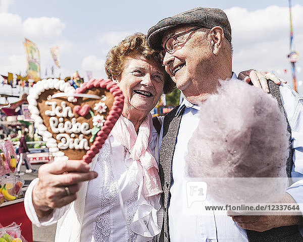Portrait of happy senior couple with gingerbread heart and cotton candy on fair