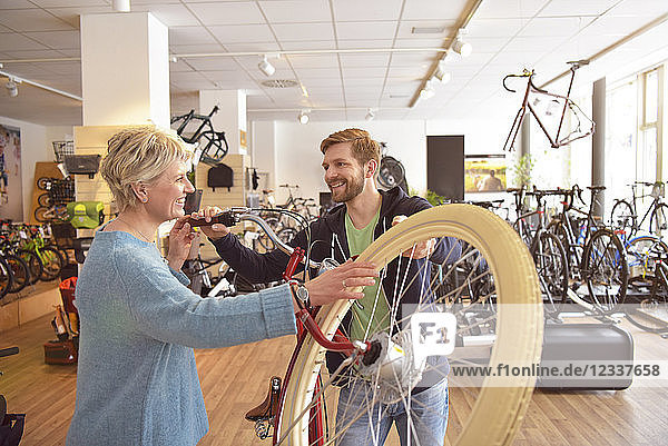 Salesperson helping customer in bicycle shop