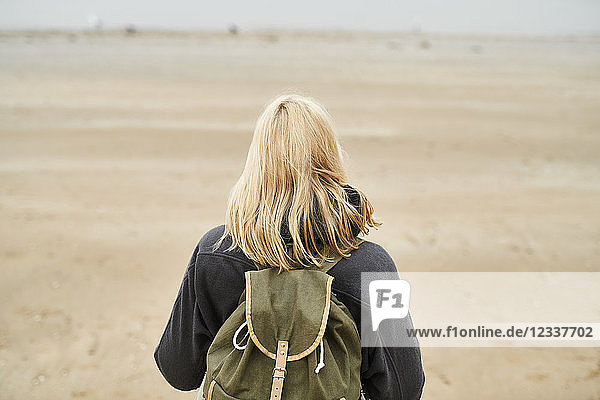 Back view of blond young woman with backpack on the beach