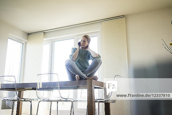 Businesswoman on the phone sitting barefoot on meeting table