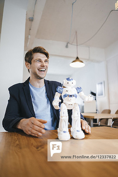 Laughing man with robot on table