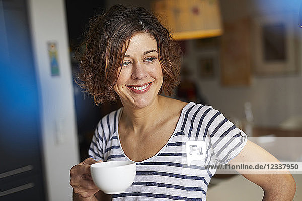Portrait of relaxed mature woman with cup of coffee at home