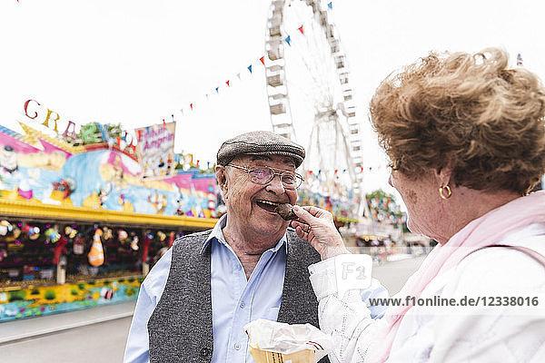 Portrait of happy senior man having fun with his wife on fair