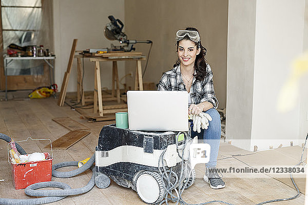 Young woman renovating her new flat  using laptop