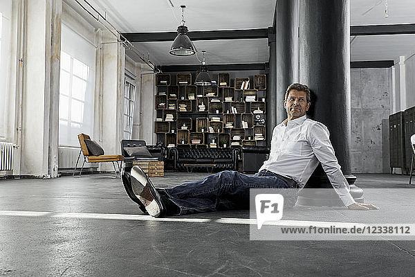 Mature man sitting on the floor in loft flat