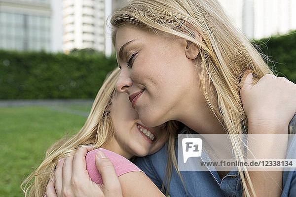 Happy mother and daughter hugging and smiling in urban city garden
