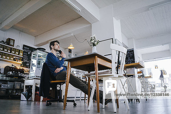 Man sitting at table in a cafe thinking