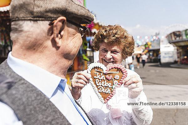 Portrait of hasmiling senior woman presenting gingerbread heart on fair