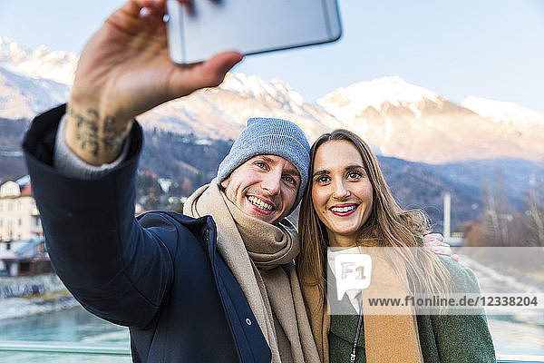Austria  Innsbruck  portrait of happy young couple taking selfie with smartphone in winter