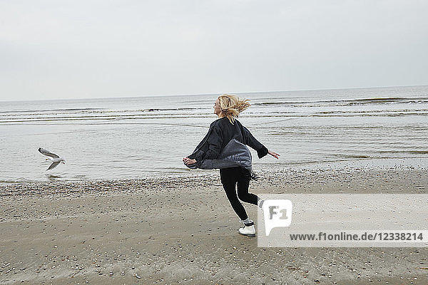 Netherlands  happy blond young woman running on the beach