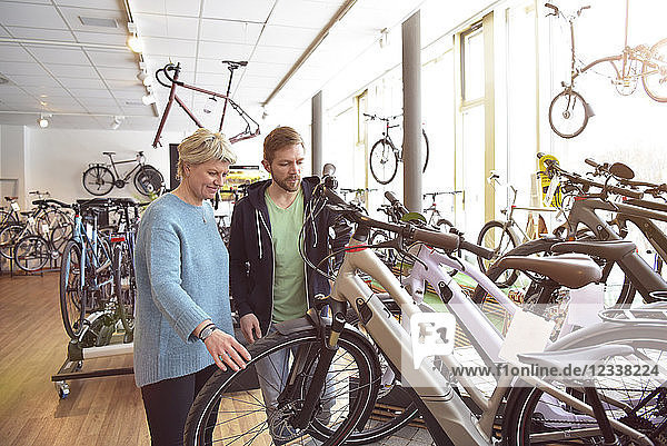 Salesman helping customer with e-bike