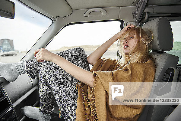 Young woman with tousled hair sitting in car